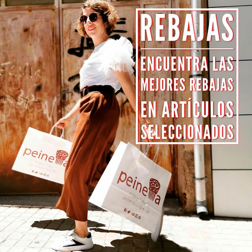 Una mujer camina por la calle con dos bolsas de papel en el que se ve la marca de Peineta. El personaje viste camiseta con flecos y falda larga marrón. Calza unas deportivas. Tiene un texto en el que anuncia las rebajas.