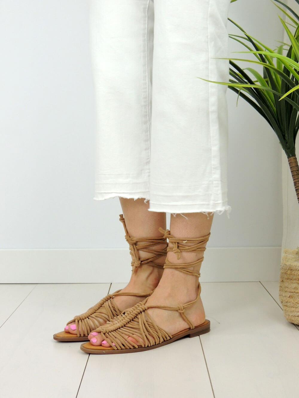 Imagen de producto. Vista de los pies de una modelo que calza una sandalias con una multitud de cuerdas que van entrelazadas entre si. Las sandalias combinan muy bien con unos pantalones blancos.