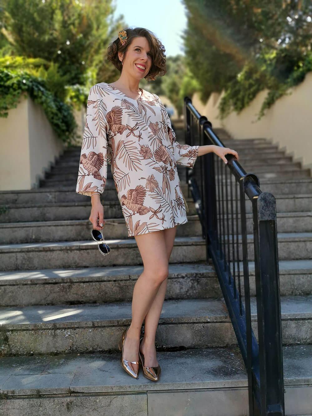 Plano entero y angulación frontal. Vista de una chica que baja por una larga escalinata. Se sujeta a a barandilla negra. Lleva un vestido corto de motivos naturales (ilustración de ramas y animales). Las figuras son de color rosa desaturado, con fondo blanco. LLeva zapatos dorados.