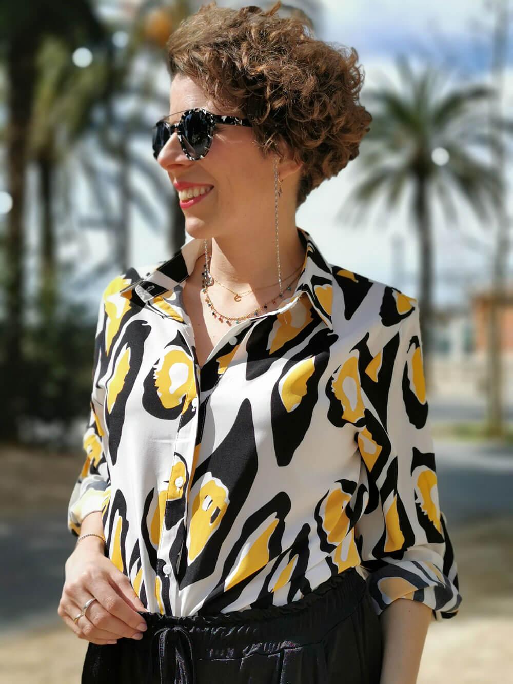 Plano medio de una chica sonriendo, sobre fondo de palmeras. Viste una camisa blanca de manga larga con manchas de color negro y amarillo. Lleva un pantalón cómodo conjuntado de color negro.