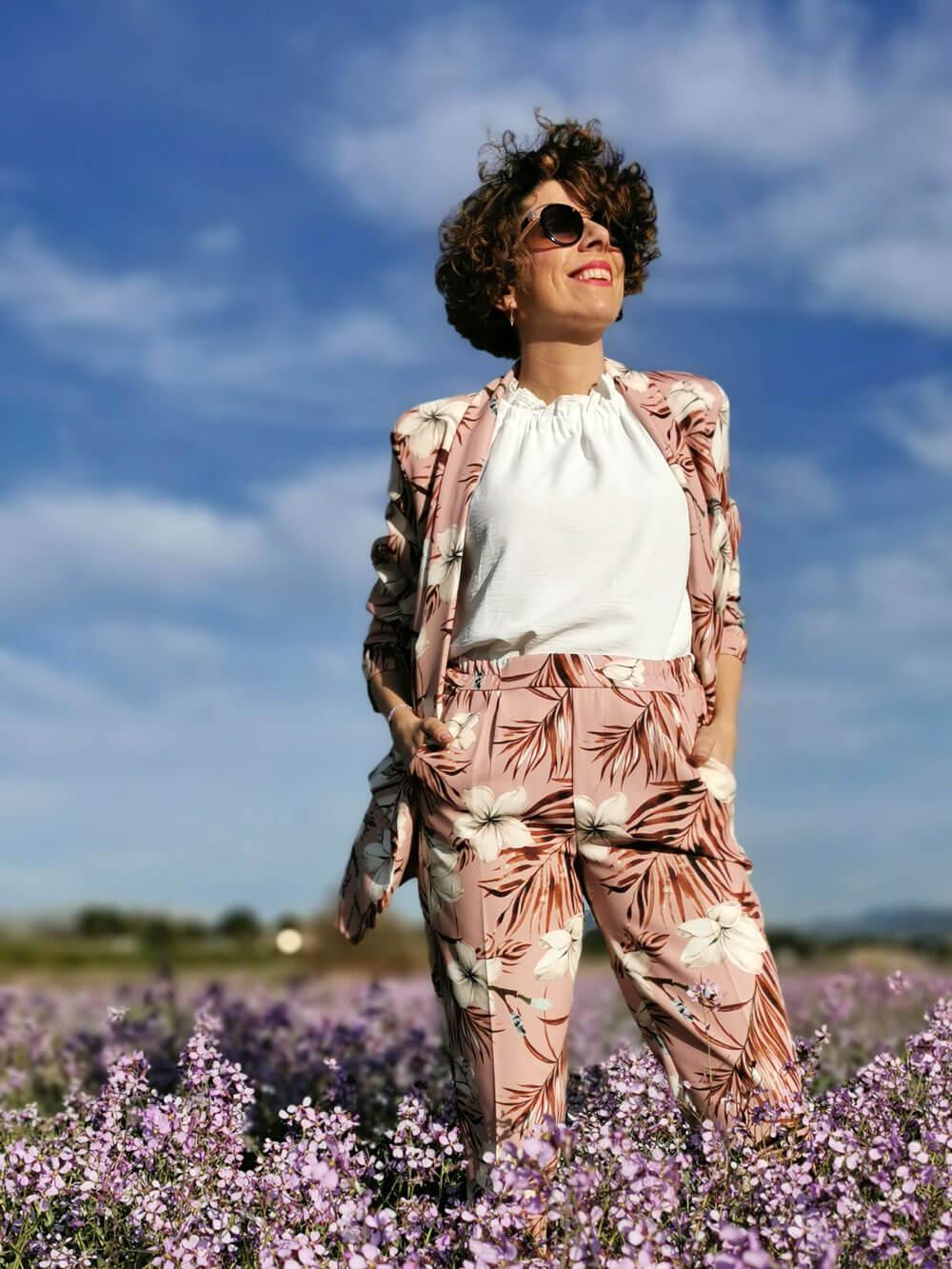 Plano americano, angulación frontal. Se ve a una mujer sonriente mirando al cielo mientras camina por un campo de flores violetas. Viste con una americana y pantalón de color rosa con motivos vegetales ramas y flores. Lleva abierta la americana y deja ver un sueter de algodón de color blanco.